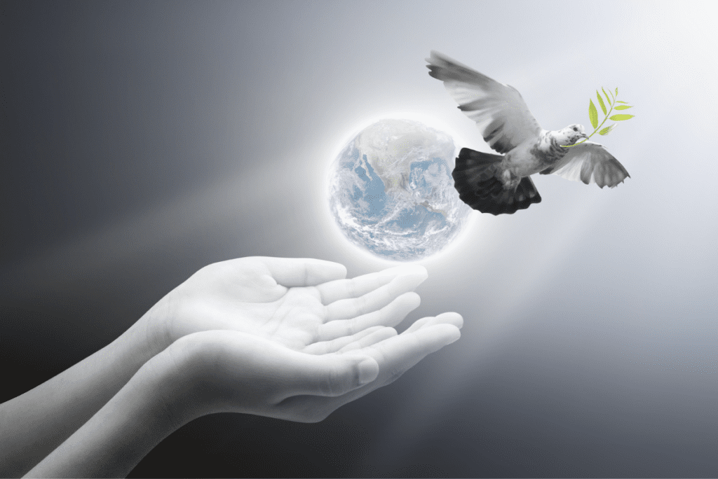 a dove flying out of a hand behind the earth