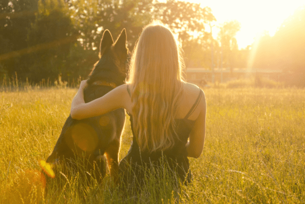 a woman and dog sitting with each other in a field