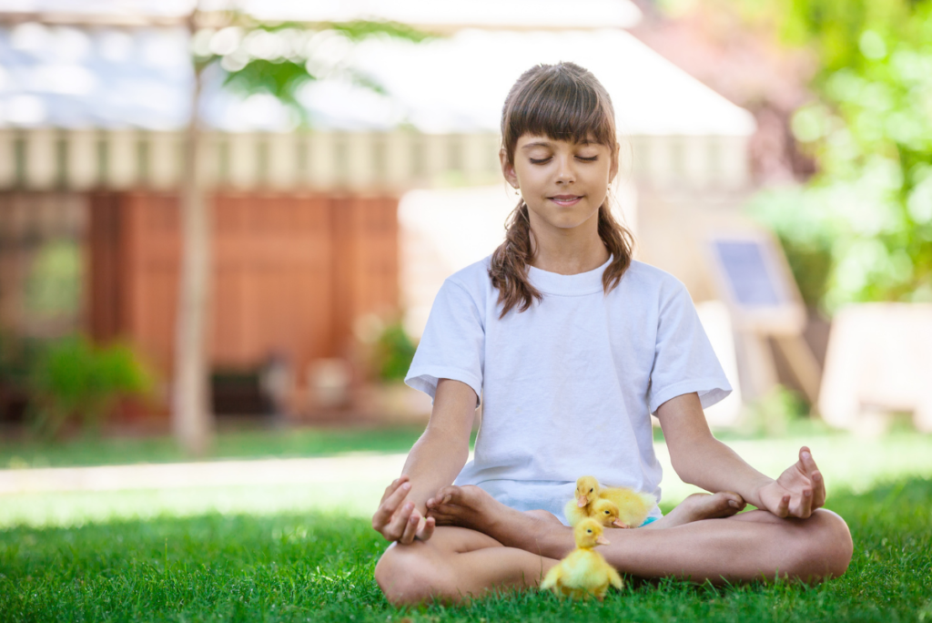a little girl meditating with baby ducklings