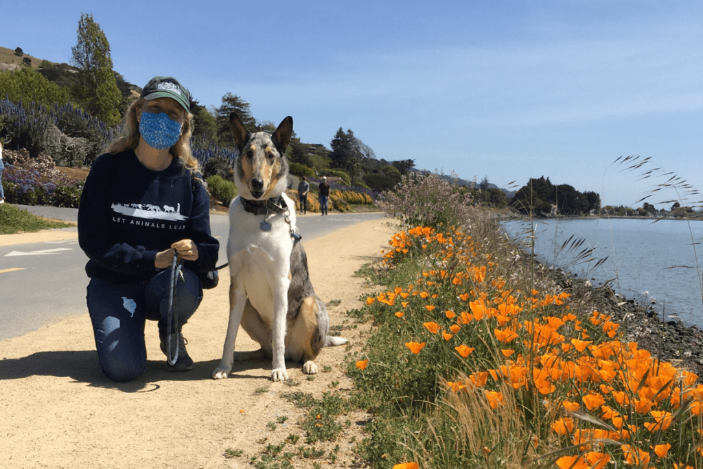 kathleen prasad next to her dog vincent by some orange flowers and water