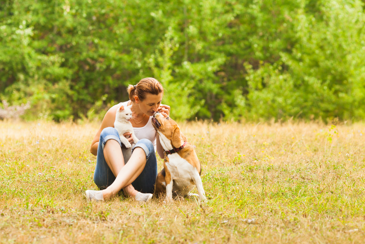 a woman sitting in a sunny field with her dog close by her side