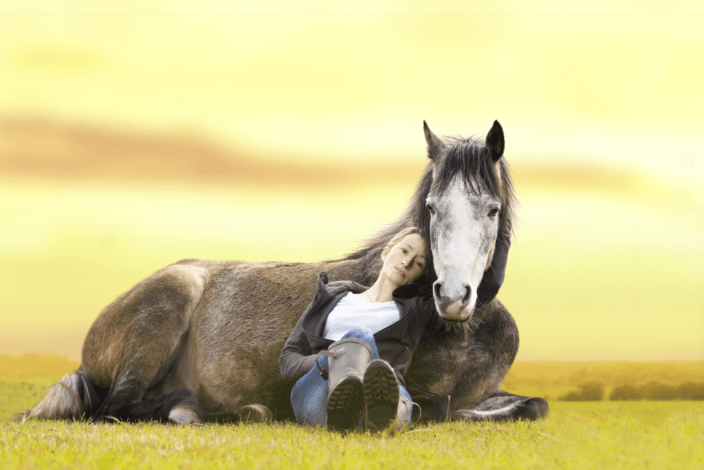 a woman laying against her horse
